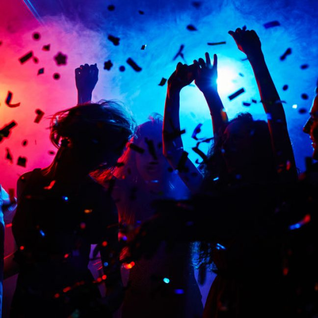 Silhouettes of dancers moving in confetti