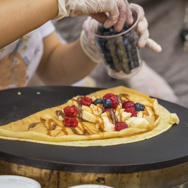 Close-up of hands of cook in gloves preparing Crepe, pancake on frying pan with fresh banana, blueberry, raspberry, sweet sauce, nutella. Concept national food, very tasty fast food, summer paty