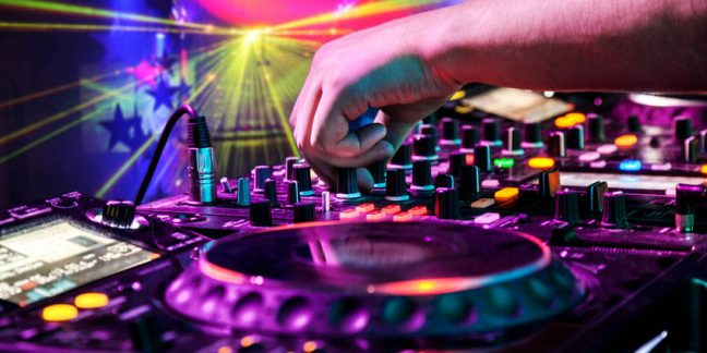 40381728 - dj mixes the track in the nightclub at party. in the background laser light show